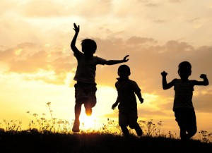 Children running on meadow at sunset